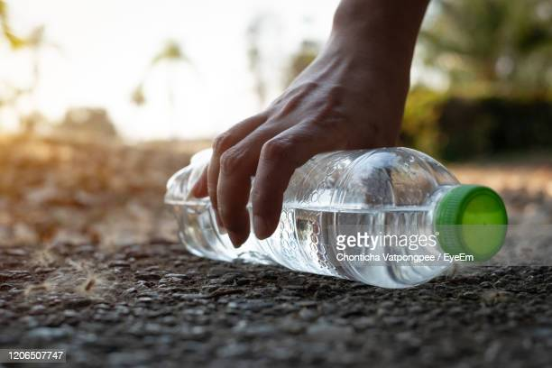 close up hand picking up clear plastic bottle water drink with a green cap on the road in the park - bottle green stock pictures, royalty-free photos & images