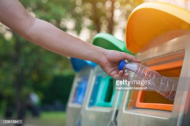 close up hand throwing empty plastic bottle into the trash, recycling concept - jetée photos et images de collection