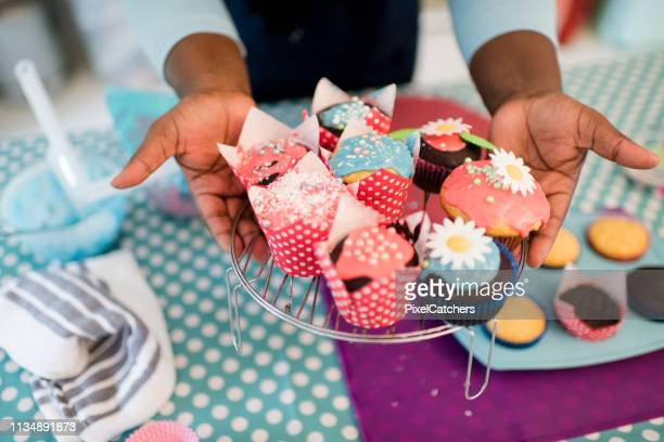 close up hands hold out brightly decorated homemade cupcakes - cake decoration stock pictures, royalty-free photos & images