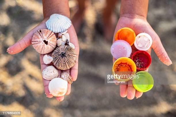 nahhände halten kunststoffe und muscheln - gift hand stock-fotos und bilder