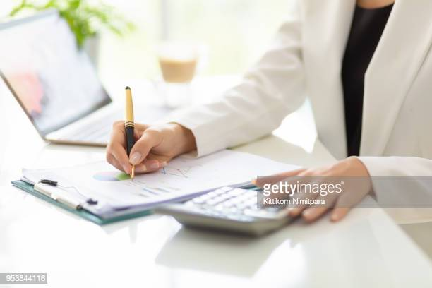 Close up hands of Businessman working with business document and laptop on the table.