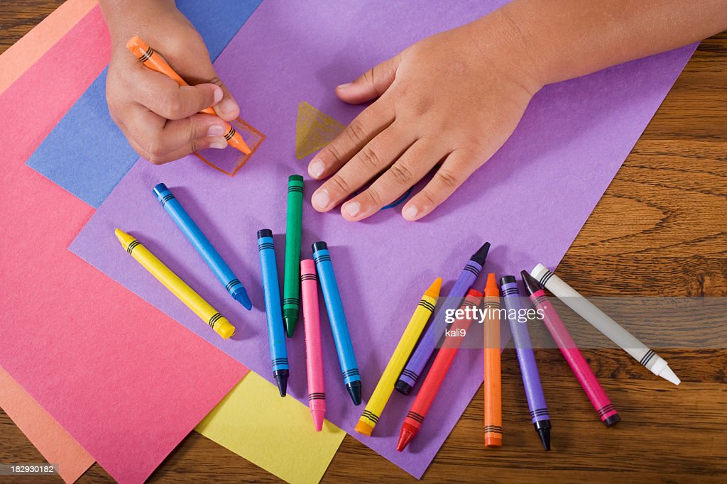 Close up hands of child drawing with colorful crayons : Bildbanksbilder