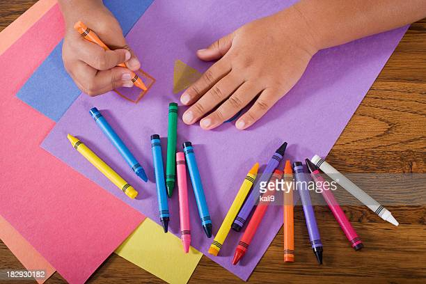 Close up hands of child drawing with colorful crayons