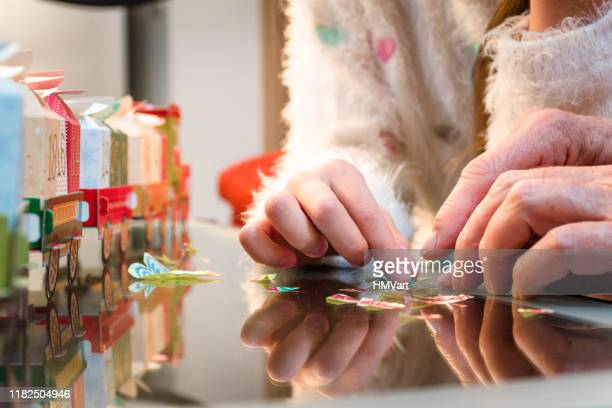 close up hands of girl with grandmother opening advent calendar - advent calendar stock photos and pictures