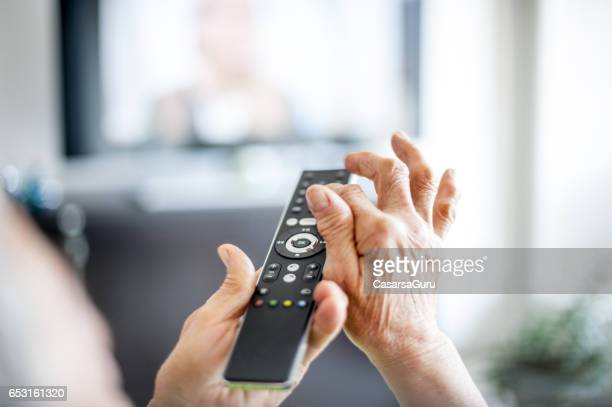 テレビのリモコンを使用して年配の女性の手を閉じる