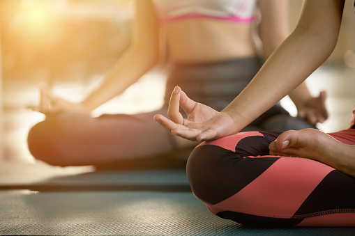 Close up hands of  Woman doing yoga exercising meditation . group of girl meditate sitting in lotus position on mat fingers in mudra at fitness gym sport club in sunrise 1126947166