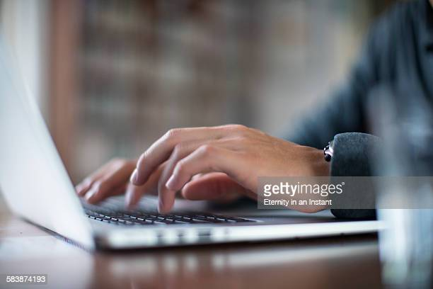 Close up hands typing on a laptop