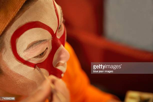 close up high angle shot of a young actor as he carefully applies traditional chinese face paint to his cheek. - chinese opera stock-fotos und bilder