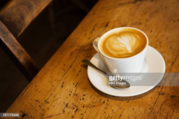 Close up high angle view of a cup of cappuccino on a rustic wooden table, heart shape in milk foam.