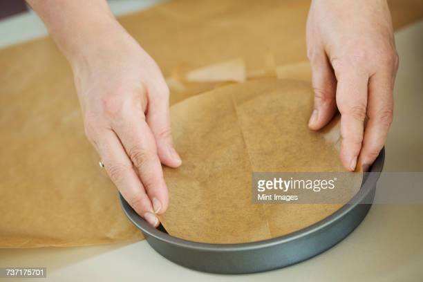 Close up high angle view of person lining the bottom of a round baking tin with baking paper.