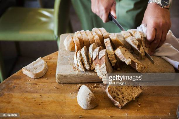 close up high angle view of person slicing freshly baked loaf of bread. - artisanal food and drink stock pictures, royalty-free photos & images
