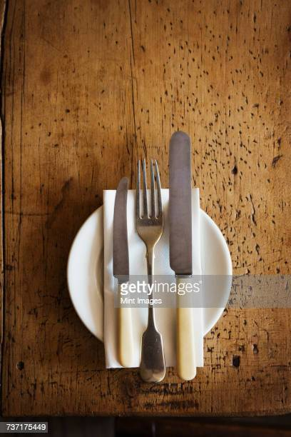 close up high angle view of plate with knives and fork and a serviette on a rustic wooden table. - fork stock pictures, royalty-free photos & images