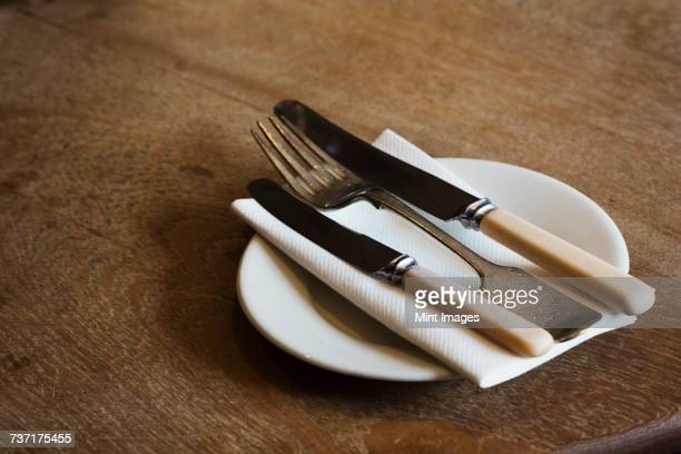 close up high angle view of plate with knives and fork and a serviette on a rustic wooden table. - faca faqueiro - fotografias e filmes do acervo