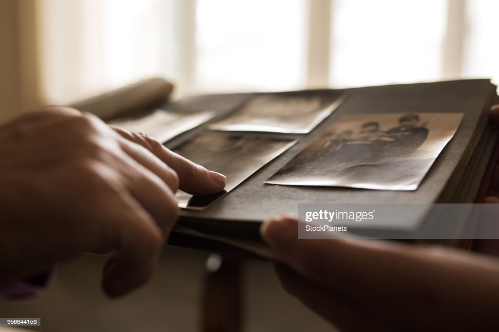 Close up human hand pointing to photo in photo album : Stock Photo