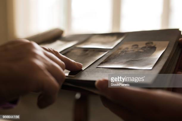 close up human hand pointing to photo in photo album - ricordi foto e immagini stock