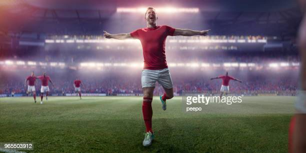 professional soccer player running with arms out in victory celebration - football player stock pictures, royalty-free photos & images