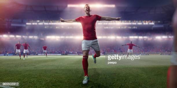 calciatore professionista che corre con le braccia fuori nella celebrazione della vittoria - calciatore foto e immagini stock