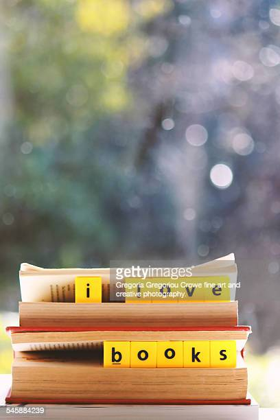 a close up image of a stack of books with scrabble - gregoria gregoriou crowe fine art and creative photography. stock-fotos und bilder