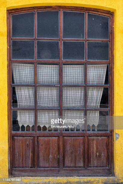 close up image of a wooden window frame with cloth curtain in buldan. - emreturanphoto stock-fotos und bilder