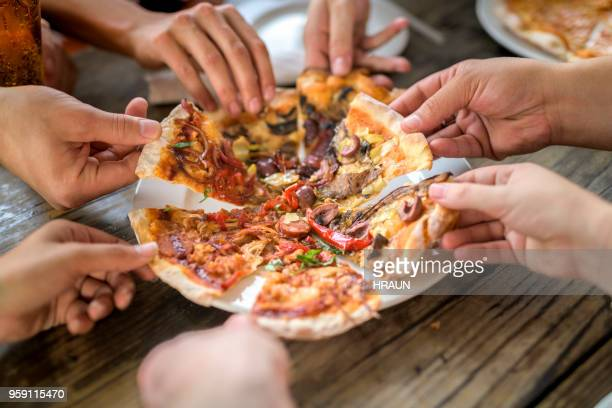 close up image of friends having pizza at bar - pizza stock photos and pictures
