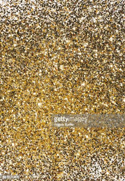 A close up image of gold glitter nail varnish or polish