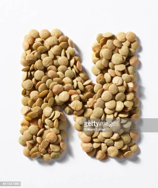 A close up image of green lentil pulses in the shape of a letter N