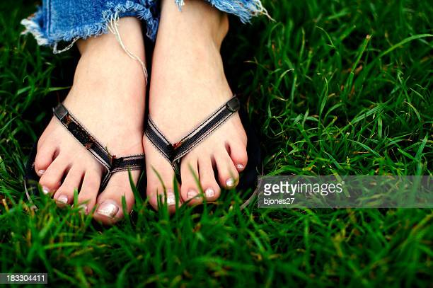 A close up image of human feet in flip flops on the grass