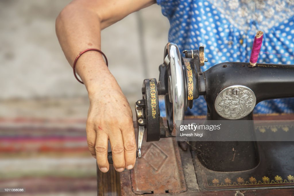 close up image of lady hands sewing her cloth with  old sewing machine : Stock Photo