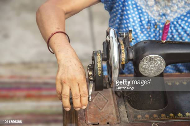 close up image of lady hands sewing her cloth with  old sewing machine - antico condizione foto e immagini stock