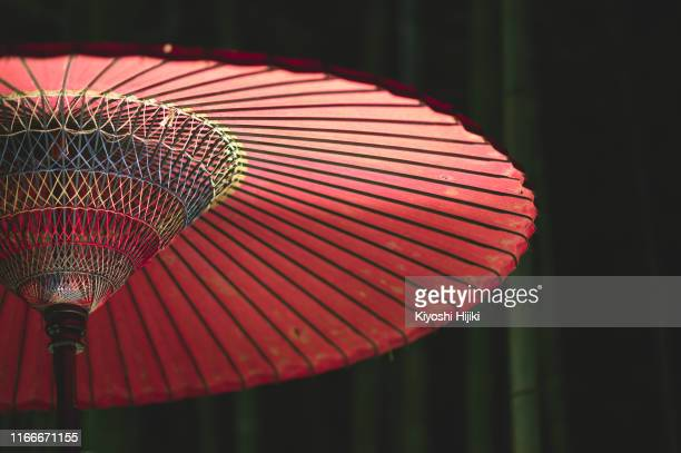close up image of red japanese umbrella against bamboo forest at night - 十月 ストックフォトと画像