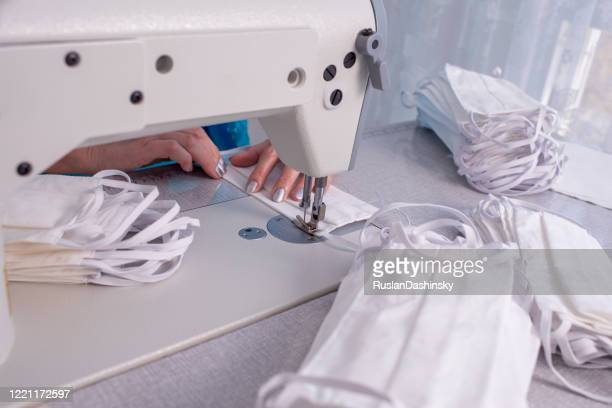 close up image of sewing machine needle and seamstress's hands sewing face masks product, stitching elastic straps to the fabric. - face mask beauty product stock pictures, royalty-free photos & images