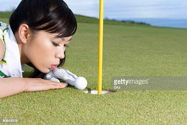 Close Up Image of Woman Blowing Golf Ball by Cup