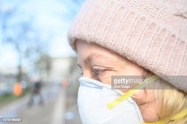 close up in a sunny day of  woman in a street wearing a protection mask. unrecognizable persons walking in a street in berlin, germany. - 1918 flu pandemic stock pictures, royalty-free photos & images