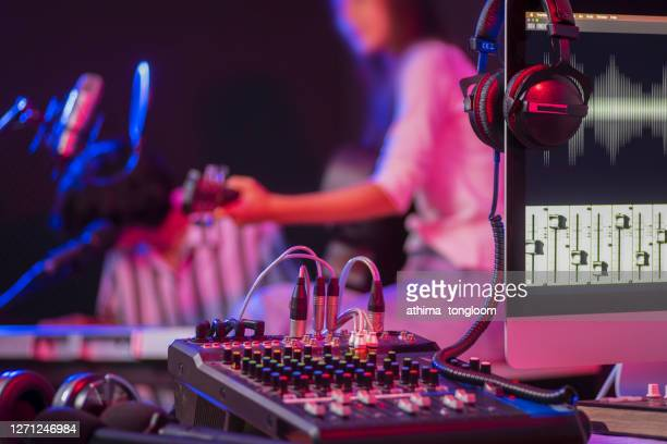 close up instruments ,musician is background. headphones hang on microphone with sound mixer board in home recording studio. - producer stock pictures, royalty-free photos & images