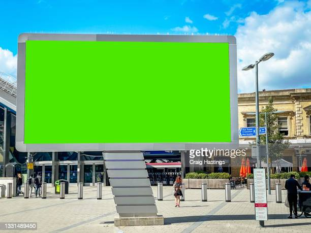 close up large green screen advertisement billboard at translation as commuters go to work. ad space, copy space chroma key, london, uk - station stock pictures, royalty-free photos & images