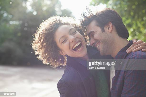 close up laughing couple hugging - interracial wife stock pictures, royalty-free photos & images