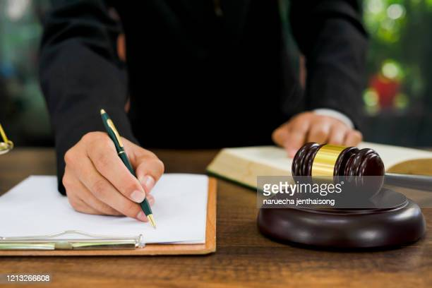 close up lawyer businessman working or reading lawbook in office workplace for consultant lawyer concept. - law stock pictures, royalty-free photos & images