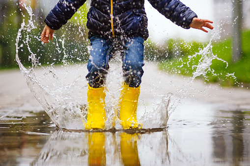 Close up legs of child with yellow rubber boots jump in puddle on an autumn walk 1148404365