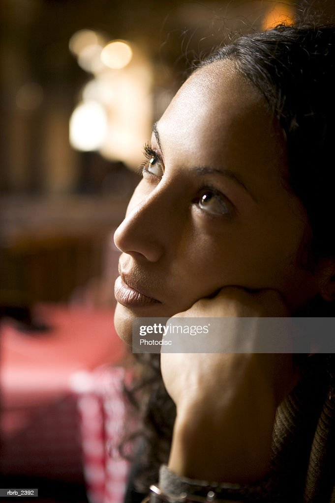 close up lifestyle shot of a young adult woman as she glances upward in thought : Foto de stock