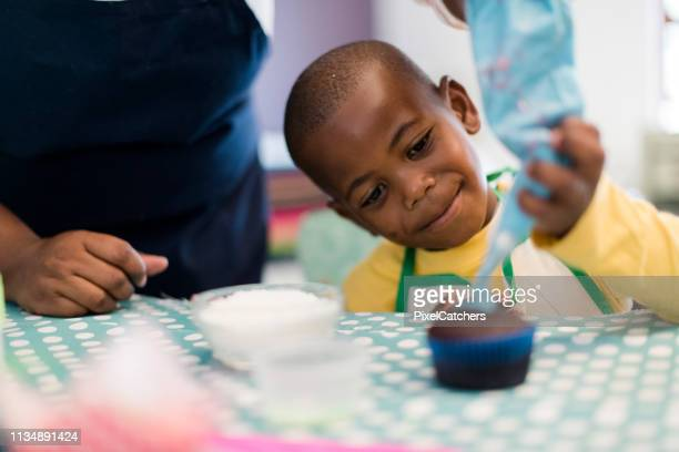 close up little boy icing cupcake with the help of his mother - decorating a cake stock pictures, royalty-free photos & images