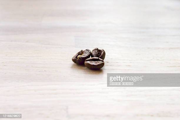 close up macro view of three roasted coffee beans on wooden table background. - small group of objects stock pictures, royalty-free photos & images