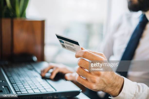 close up male hand holding credit card paid online - penalty stock pictures, royalty-free photos & images