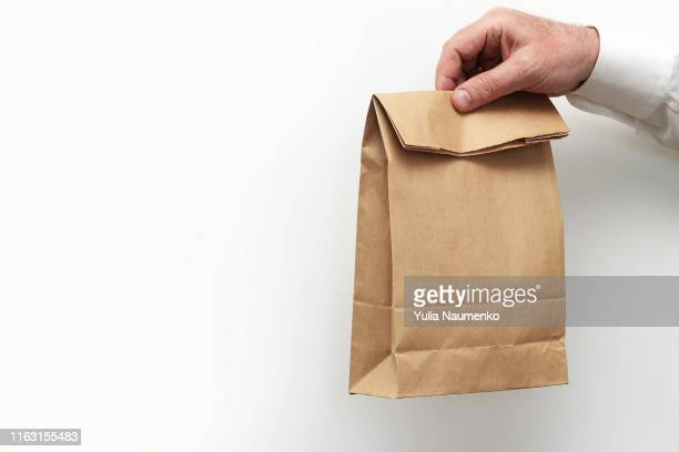 close up male holds in hand clear empty blank craft paper bag for takeaway isolated on white background. packaging template mock up. delivery service concept. copy space. - bag photos et images de collection