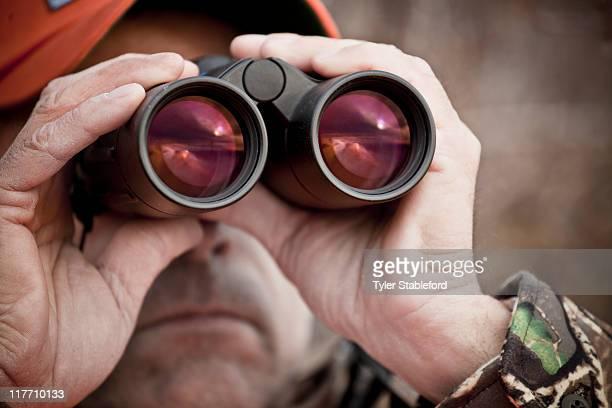 close up, male hunter looking through binoculars. - 狩人 ストックフォトと画像
