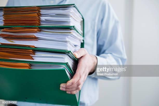 Close up man carrying pile filing folders