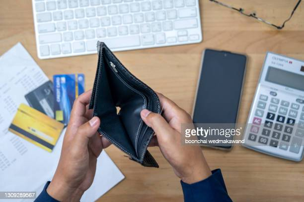 close up man hand opening empty wallet over calculator. - failure stock pictures, royalty-free photos & images