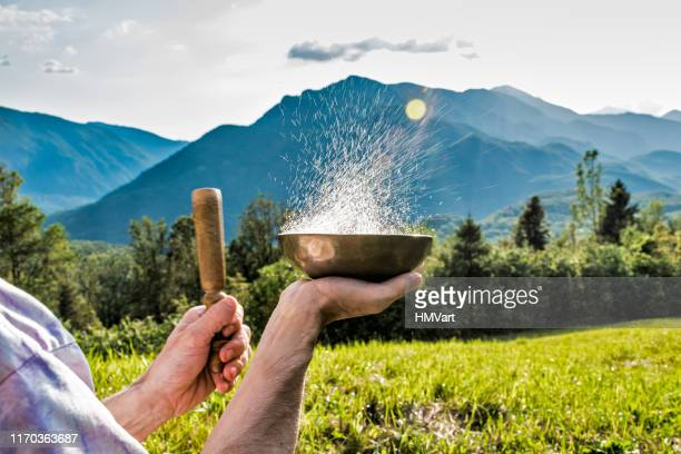 close up man hands playing tibetan handcrafted singing bowls against mountain at the sunset - rin gong stock pictures, royalty-free photos & images