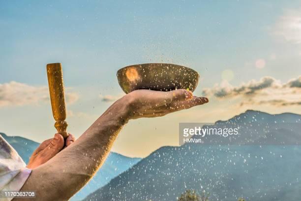 close-up man handen spelen tibetaanse handgemaakte zingende kommen tegen de berg bij de zonsondergang - tibetaanse cultuur stockfoto's en -beelden