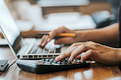 Close up man hands using a calculator and laptop computer for calculating with finance paper, tax, accounting, Accountant concept.