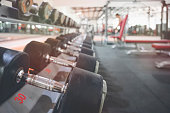 Close up many metal dumbbells on rack in sport fitness center